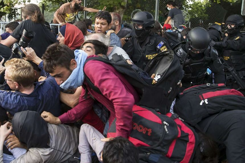 Hungarian riot police fight migrants at the border crossing with Serbia in Roszke, Hungary.