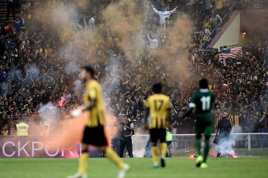 Malaysian football fans throw flares onto the pitch during the 2018 FIFA World Cup qualifying football match between Malaysia and Saudi Arabia in Shah Alam on Sept 8, 2015.