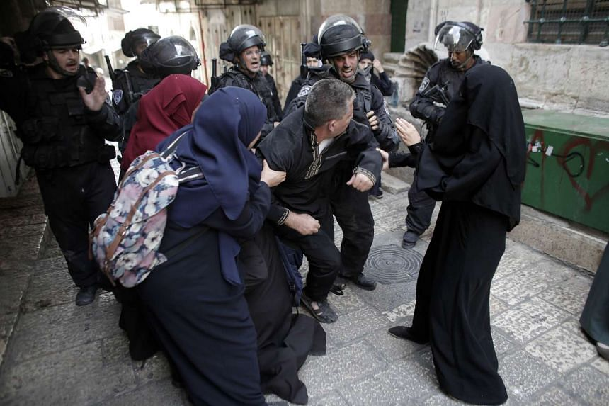 Palestinians scuffle with Israeli riot police after security forces blocked a road leading to the Al-Aqsa mosque compound in Jerusalem's Old City on Sept 14, 2015.