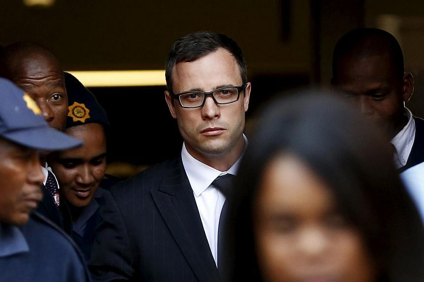 Oscar Pistorius leaves after listening to the closing arguments in his murder trial at the high court in Pretoria in this Aug 7, 2014 file photo.