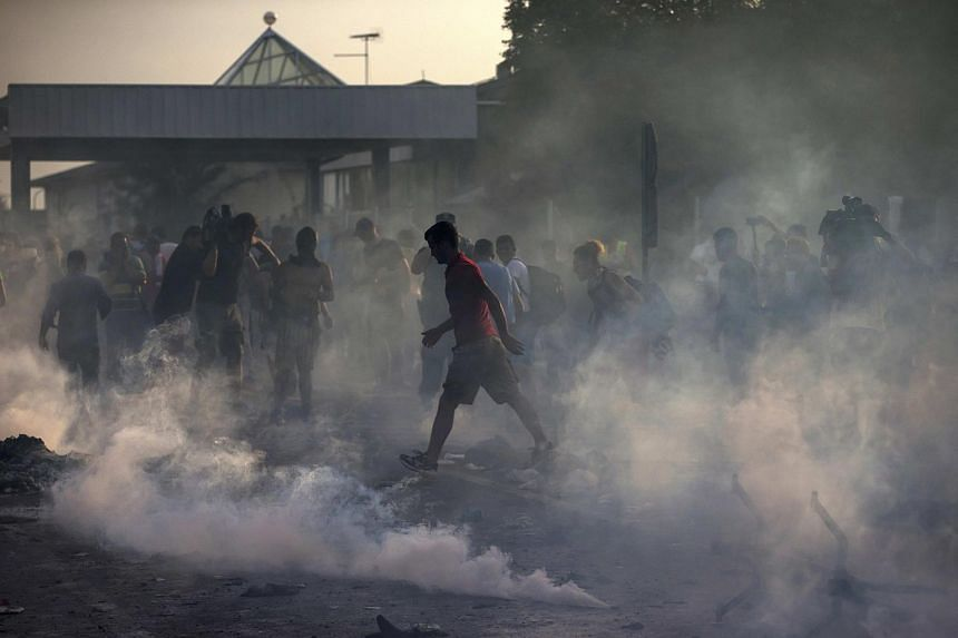 Migrants clashing with Hungarian riot police at the border crossing with Serbia in Roszke, Hungary on Sept 16, 2015.