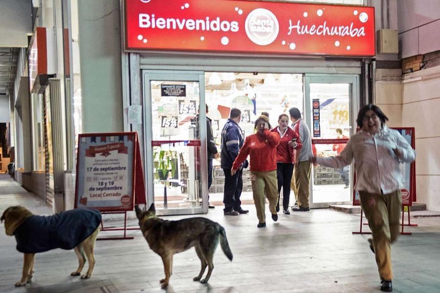 Shoppers running out of a supermarket at a strong quake struck Santiago on Sept 16, 2015.