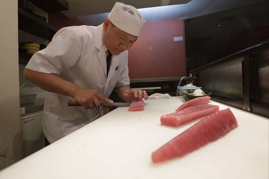 Chef Kevin Yong at Hinoki Japanese Dining preparing a bluefin tuna dish yesterday. In an effort to be more environmentally sustainable, the restaurant will not serve bluefin tuna, one of its most popular dishes, for three weeks next month.
