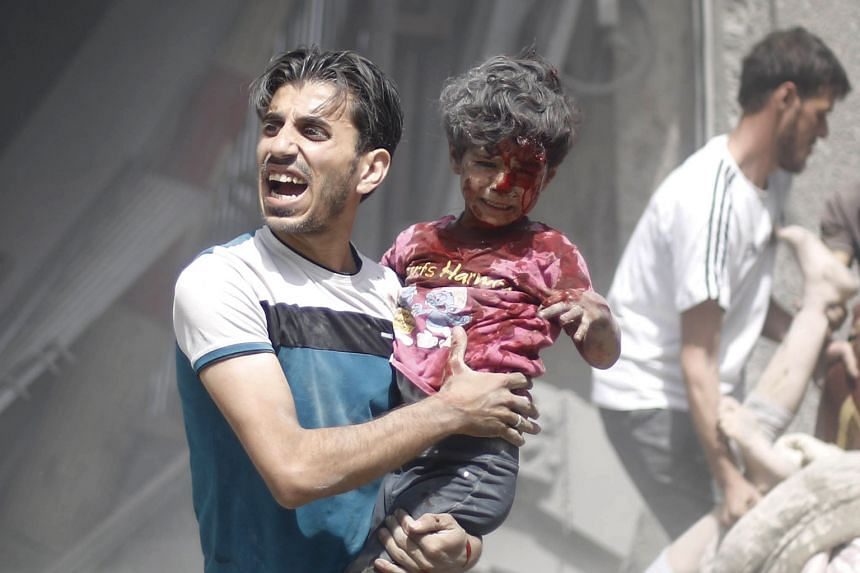 A Syrian man carrying a wounded child after a reported air strike by government forces in Douma, east of Damascus, on Aug 30.