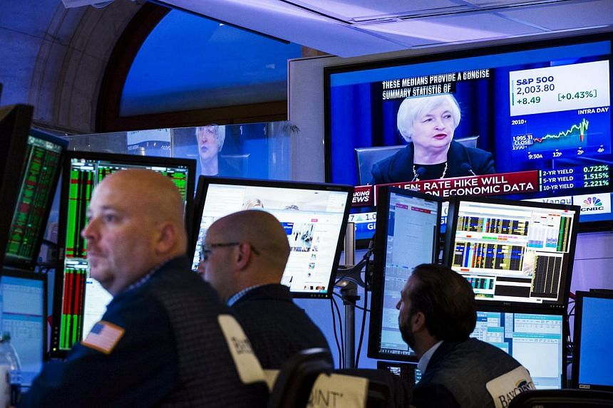 Traders working underneath a television screen showing Federal Reserve Chair Janet Yellen announcing that the Federal Reserve will leave interest rates unchanged.