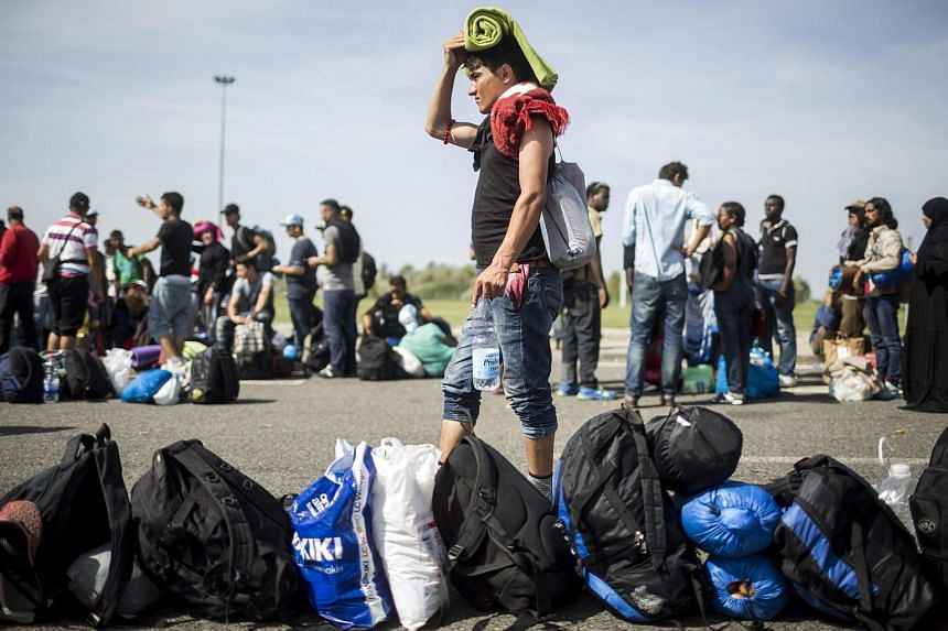 Migrants waiting for a bus at the closed border crossing between Serbia and Hungary on Sept 17, 2015.