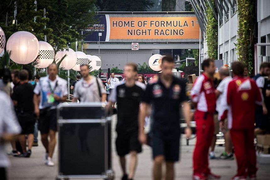 Formula One team members walk in the paddock ahead of the Formula One Singapore Grand Prix in Singapore on Sept 17, 2015.