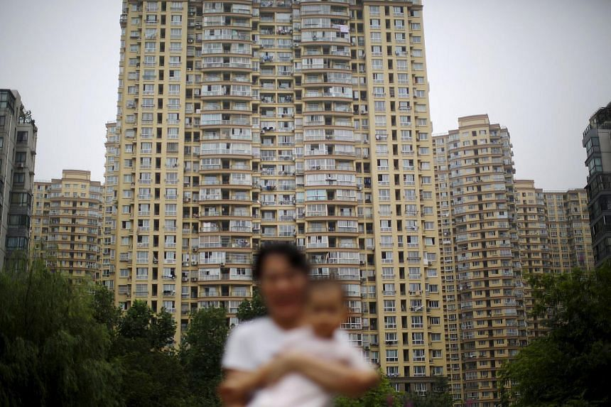 A woman holding her son at a playground in a residential area in Shanghai.