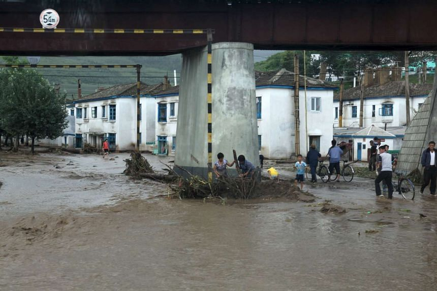 Residents attempt to clear flood debris from under a bridge in North Korea in this file photo from Aug 22, 2015.