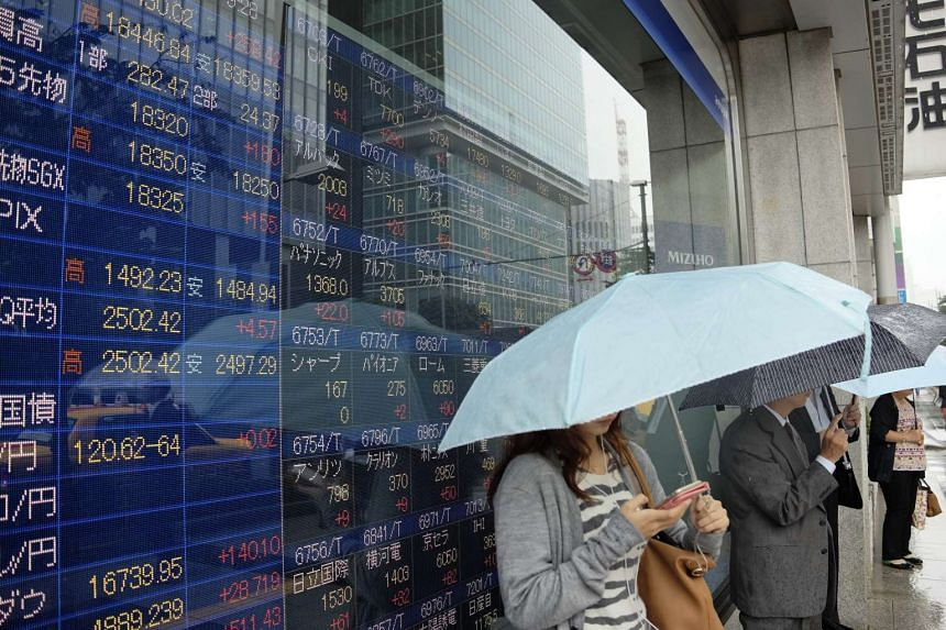Pedestrians stand in front of a board showing various share prices on the Nikkei 225 index on Sept 17, 2015.