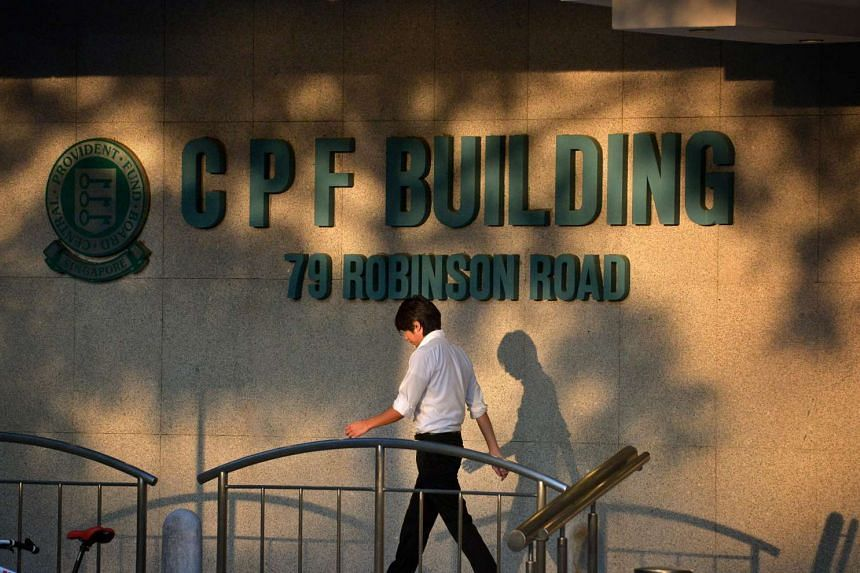 People walking past the CPF Building logo at the foot of the building along Robinson Road.