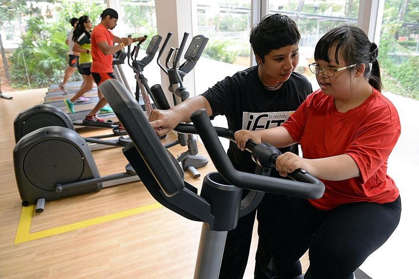 """Singapore's first """"inclusive"""" gym - open to everyone, including people with disabilities and the elderly - officially opened in Lengkok Bahru yesterday. Among the first to try out the gym equipment was Ms Felicia Lee, 23, (right), who has an intellec"""