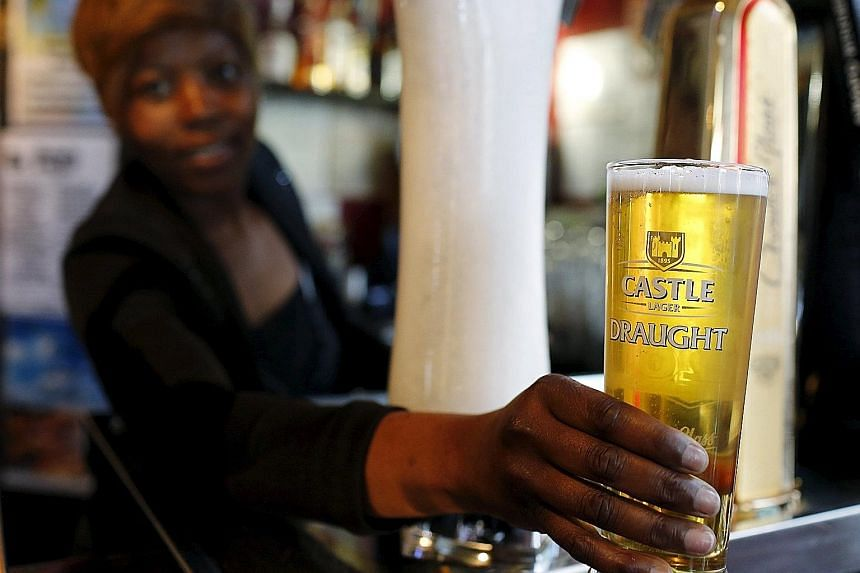 A bartender serving a beer produced by SABMiller at a bar in Cape Town. Speculation on rival brewer Anheuser-Busch InBev's takeover approach on Tuesday sent London-based SABMiller's shares up as much as 4.1 per cent.