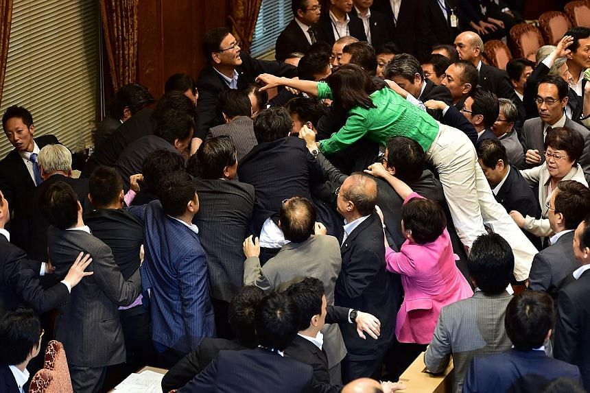 Japanese lawmakers scuffling at the Upper House's ad hoc committee session for the security Bills yesterday. But the mad-dash tactics, uncommon in the normally sedate Parliament, failed to stop the Bills from being approved by the legislative committ