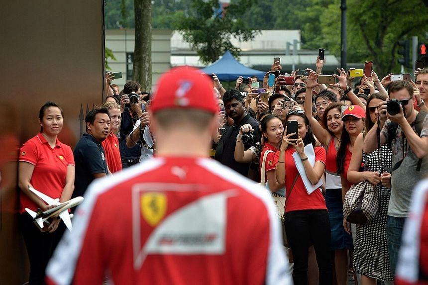 All eyes are on Ferrari's Kimi Raikkonen when he arrives at a UPS event in front of Raffles City (left). The Finn is at ease in an interview at the Shell Trackside Laboratory (above), noting that his team have gone into overdrive to make changes for