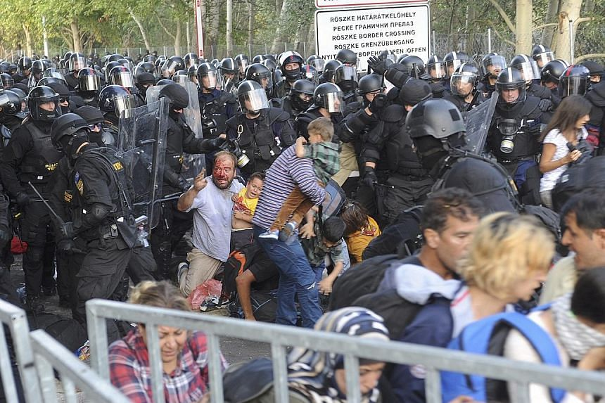 Hungarian riot police charging at migrants at the border with Serbia in Roszke, Hungary, on Wednesday. Meanwhile, water cannons were used on more migrants at the Hungarian border near Horgos, Serbia, on the same day.