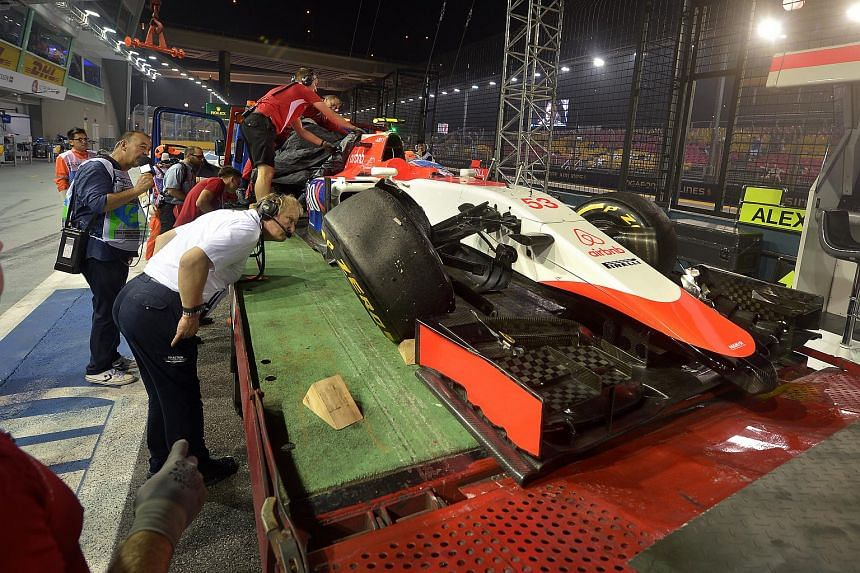 The crashed car of Manor Marussia's Alexandra Rossi is brought into the pit lane.