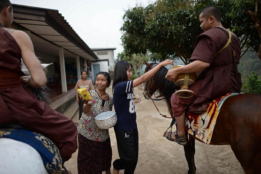 "Residents offering alms to horse-riding monks during their early morning alms-collecting round around the ""Temple of the Golden Horse"" in this April 8, 2015 file photo."