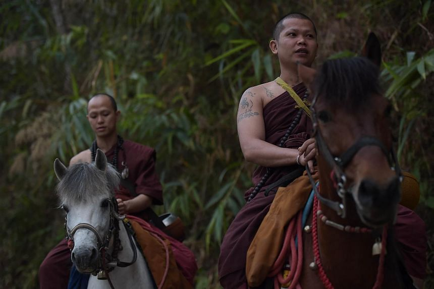 "Buddhist monks riding horses as they take part in early morning alms-collecting around the ""Temple of the Golden Horse"" in this April 8, 2015 file photo."