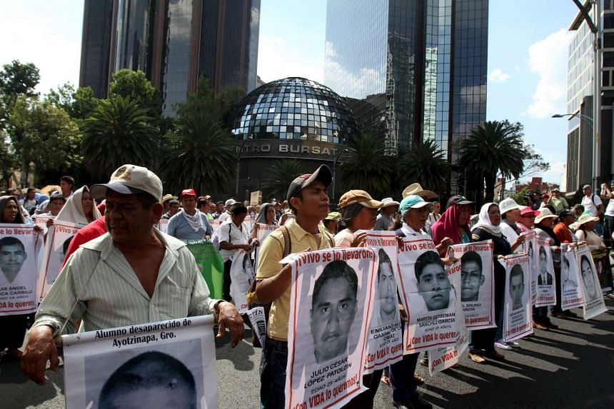 Relatives carry photos of some of the 43 missing students at a march in Mexico City.