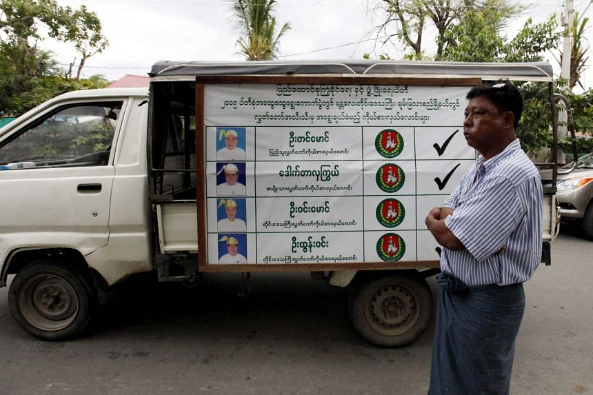 A man stands near campaign posters of the ruling Union Solidarity and Development Party (USDP) in Mandalay, Myanmar on Sept 18, 2015.