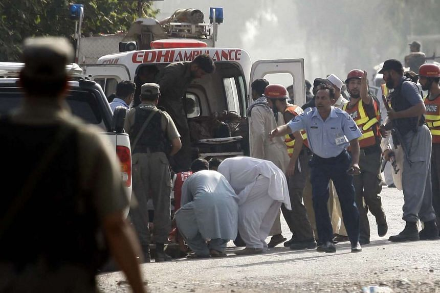 Emergency teams transfer unidentified bodies and injured victims with ambulances after militants attacked a Pakistan Air Force (PAF) base on the outskirts of Peshawar, Pakistan, on Sept 18, 2015.