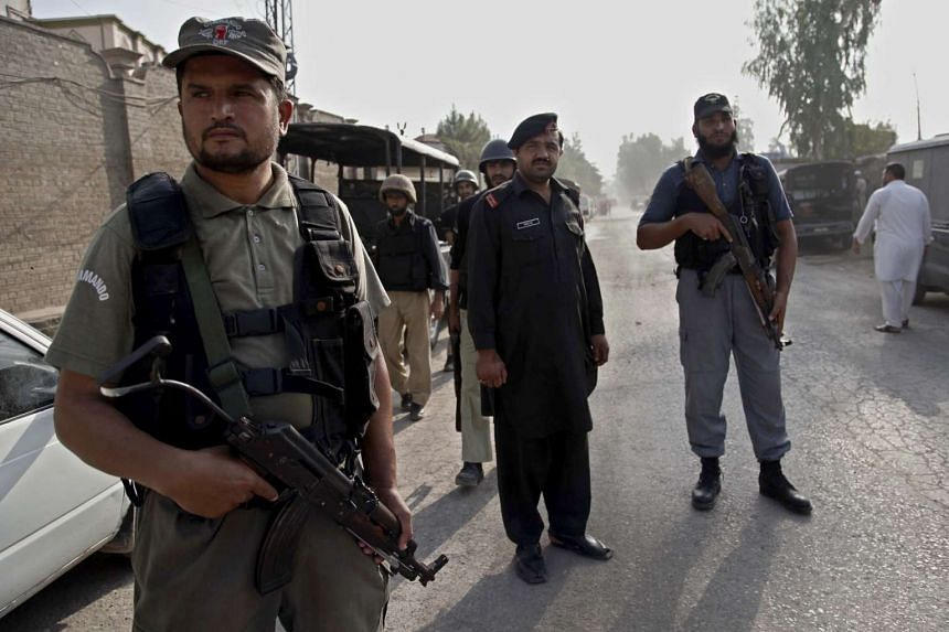 Pakistani Army soldiers block the road leading to a Pakistan Air Force (PAF) base during clashes with militants, on the outskirts of Peshawar, Pakistan on Sept 18, 2015.