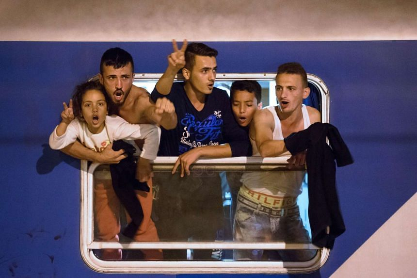 Migrants react as they wait in a train at a railway station near the Slovenian-Croatian border on Sept 17, 2015.