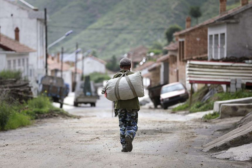 A local villager carries a sack at a village in Chongli county of Zhangjiakou on July 29, 2015.