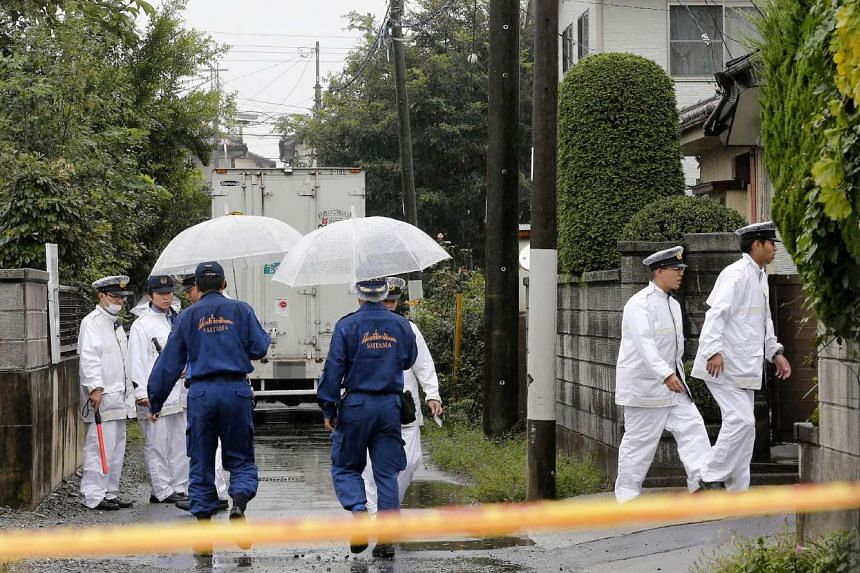 Police investigate the area around a murder scene in Kumagaya, Saitama prefecture, where six people were found stabbed to death.