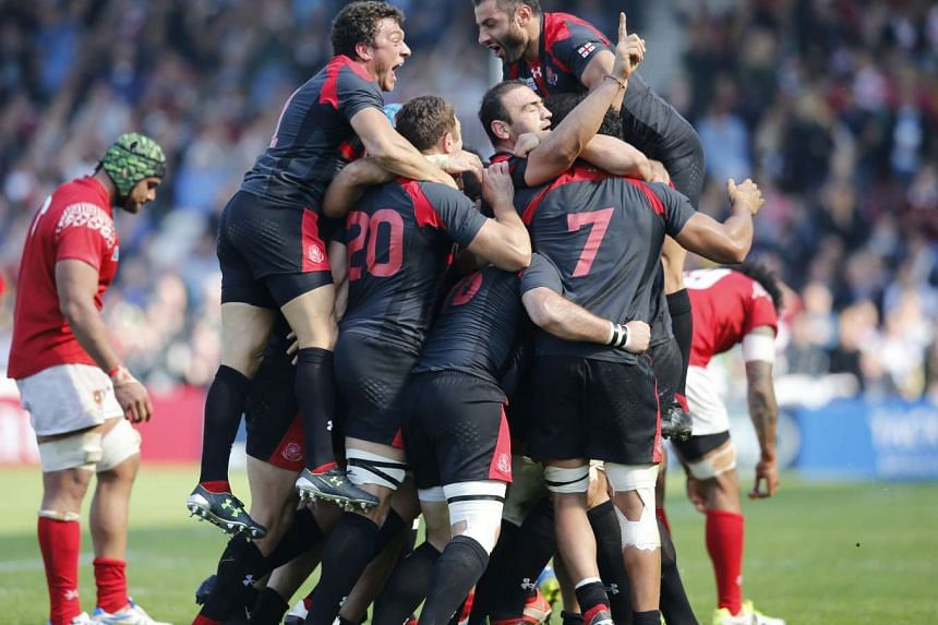 Georgia players celebrating at the end of the upset against Tonga.
