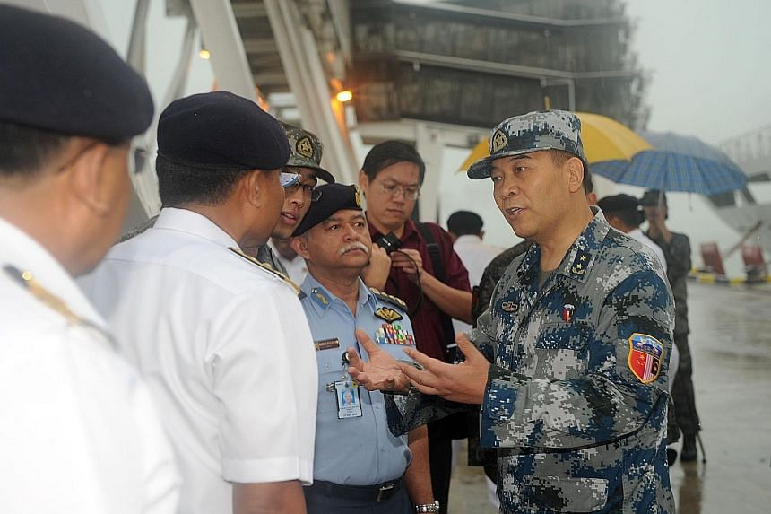Deputy Chief of General Staff of the Chinese PLA Yi Xiaoguang (above, right) talking to Malaysian military officers as Chinese navy vessels (left) arrived for the joint military exercise in Port Klang, Malaysia, on Thursday.