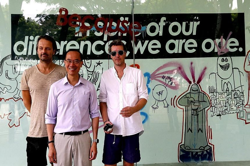 Mr George Yeo, flanked by German artists Niklas Bo Beckert (left) and Dennis Kaun, at the unveiling of a mural wall featuring graffiti art by the duo at Bedok Reservoir Park yesterday. They were also responsible for the artwork on four Berlin Wall pa