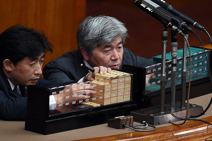 Ballots being counted in Parliament in Tokyo yesterday. The security Bills were expected to pass as Japanese Prime Minister Shinzo Abe's ruling coalition holds a majority in both houses of Parliament.
