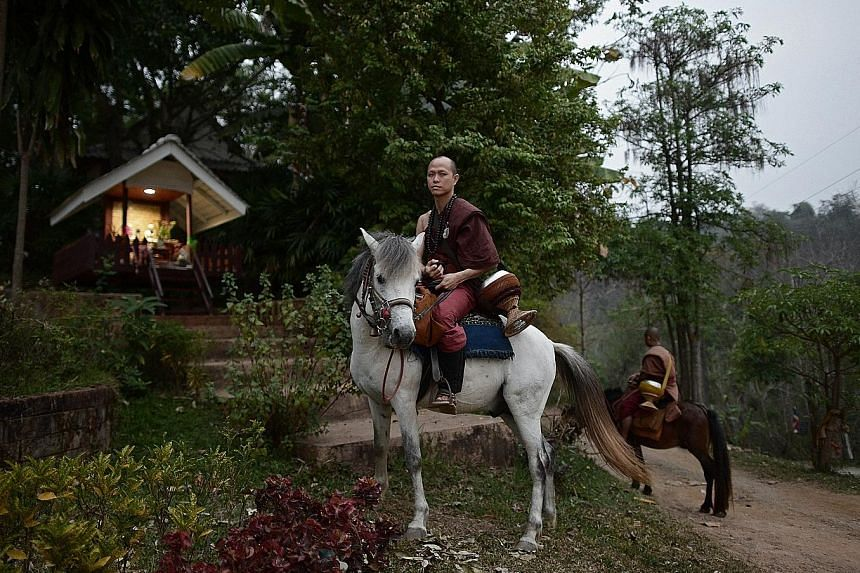 Buddhist novice Ponsakorn Mayer leaving the Temple of the Golden Horse on horseback with other monks to collect alms. His father was a drug addict and did not work.