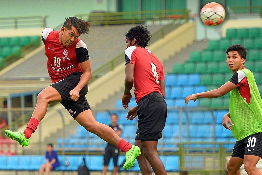 Khairul Amri (No. 19) winning a header against LionsXII team-mate Madhu Mohana during training at Jalan Besar Stadium yesterday. The forward has plundered nine goals in the Malaysian Super League and the Malaysian FA Cup.