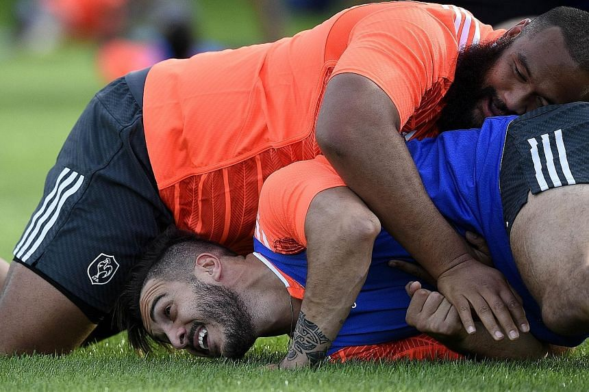 France's Sofiane Guitoune (below) feeling the full weight of his team-mate, prop Uini Atonio, during a training session at the Trinity School in Croydon this week. Atonio, who weighs 141kg, is the heaviest player in the Rugby World Cup.