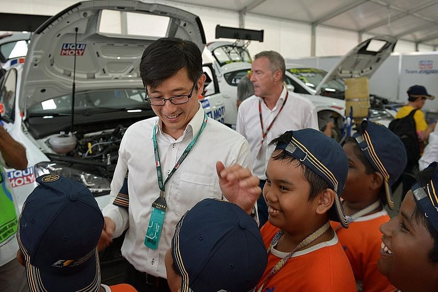 Minister of State for Trade and Industry, Mr Teo Ser Luck, with kids from five local voluntary welfare organisations at the Singapore Airlines Singapore Grand Prix yesterday. The 84 kids enjoyed a full F1 experience, enjoying the sights and sounds of