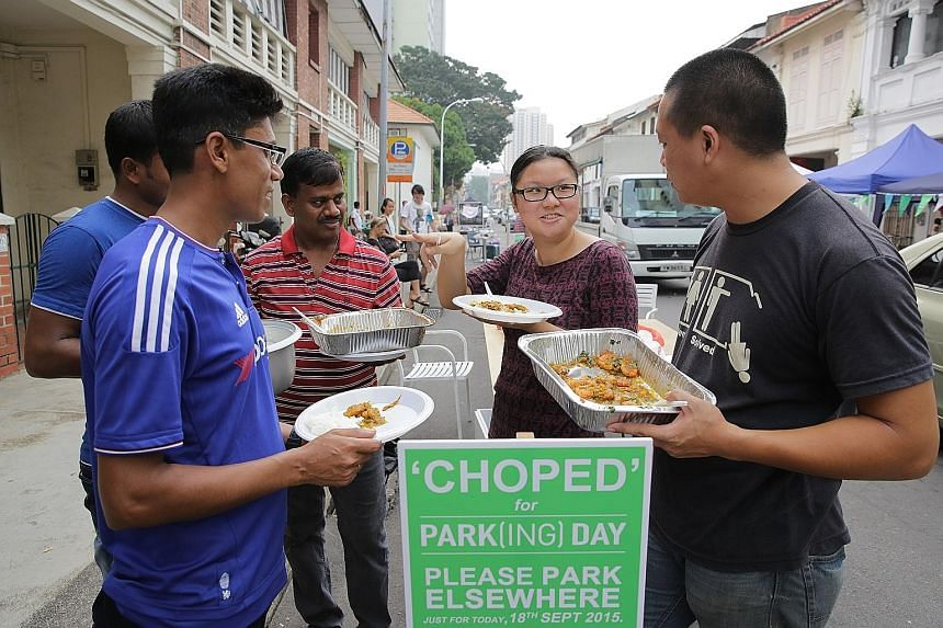 Construction firm boss Shannon Lim and his employees (from left) Farhad Hossain (partially blocked), Monir Hossain and Kasinathan Thirunavukarasu interacting with participant Toh Yi Rong at a Park(ing) Day event yesterday in Little India. They served