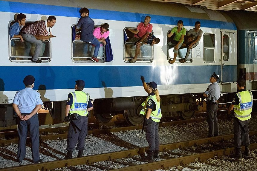 Migrants sitting on the windows of a train at the railway station near the border between Slovenia and Croatia on Thursday.