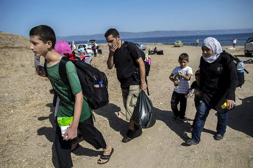 Migrants from Aleppo, war-torn Syria, walking at the beach after arriving on the Greek island of Lesbos on Sept 11, 2015.