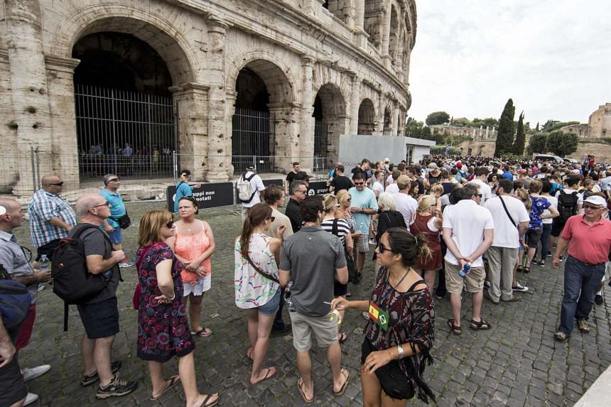 Tourists wait outside the closed Colosseum in Rome, Italy, Sept 18, 2015.