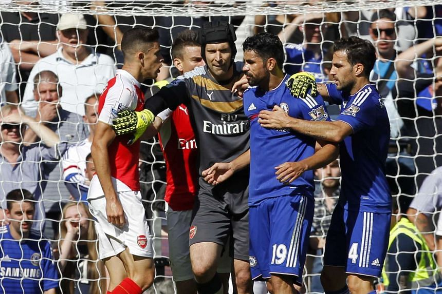 Arsenal's Gabriel (left) and Chelsea's Costa (second right) are separated by Arsenal goalkeeper Petr Cech (centre) as they clash.
