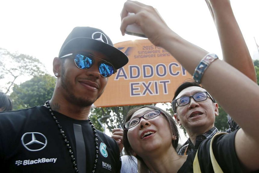 Hamilton (left) poses for a photograph with fans as he arrives at the Marina Bay street circuit.