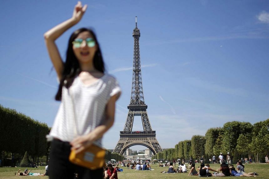 A tourist poses for a photo souvenir in front of the Eiffel Tower in Paris.