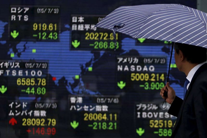 A pedestrian looking at an electronic board the stock market indices of various countries outside a brokerage in Tokyo, Japan.