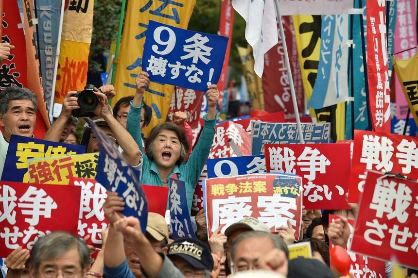 Demonstrators holding placards to protest against PM Shinzo Abe's controversial security bills in front of the National Diet in Tokyo on on Sept 18, 2015.