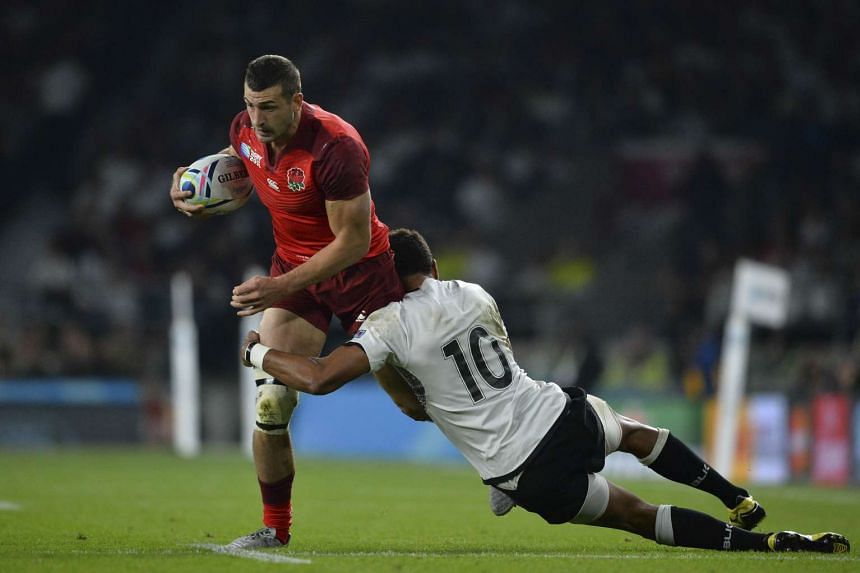 England winger Jonny May (left) is tackled by Fiji's fly-half Ben Volavola.