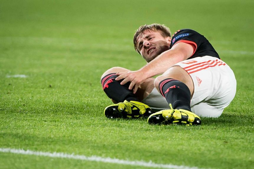 Shaw reacts in pain and hold his right leg during the UEFA Champions League match between PSV Eindhoven and Manchester United.