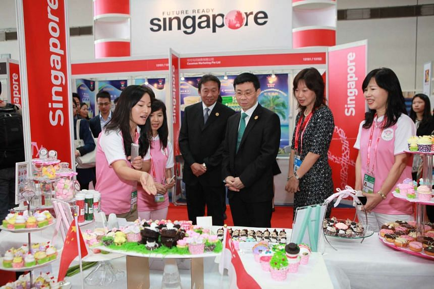 Senior Minister of State for Trade and Industry Lee Yi Shyan (wearing a green tie) visiting the Singapore Pavilion at the China-Asean Expo on Thursday.
